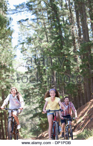 Family riding bicycles in woods - Stock Photo