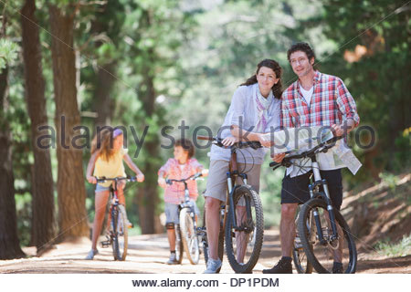 Family with bicycles looking at map in woods - Stock Photo