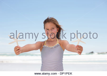 Girl holding starfish on beach - Stock Photo