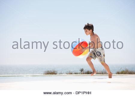 Boy holding beach ball beside pool - Stock Photo