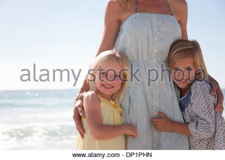 Girls hugging mother on beach - Stock Photo