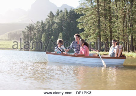 Family fishing in boat on lake - Stock Photo