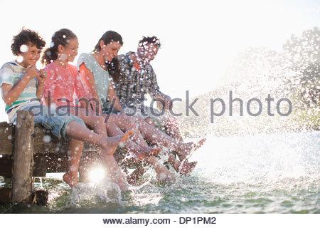 Family on dock splashing feet in lake - Stock Photo