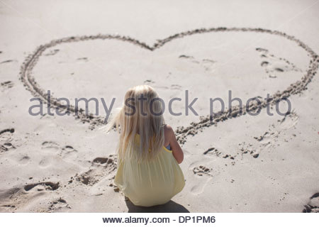 Girl drawing heart in sand on beach - Stock Photo