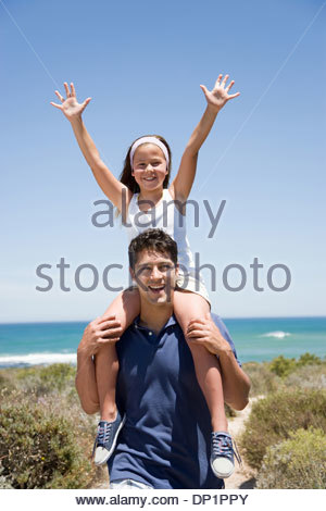 Father carrying daughter on shoulders on beach path - Stock Photo