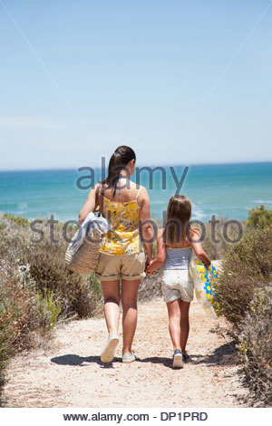 Mother and daughter walking on beach path - Stock Photo