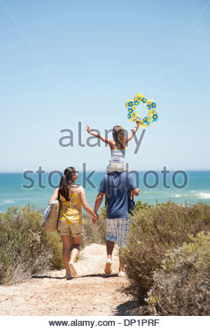 Family walking on beach path toward ocean - Stock Photo