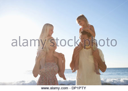 Parents carrying daughters on shoulders on beach - Stock Photo
