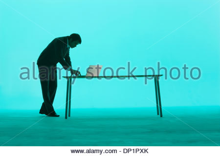 Businessman by a table using laptop - Stock Photo