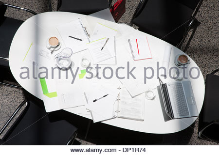 Directly above paperwork, coffee, laptops and notebooks on conference table - Stock Photo