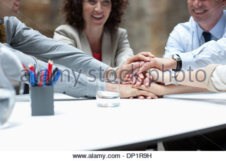Business people stacking hands in meeting - Stock Photo