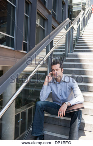 Man sitting on stairs and talking on cell phone - Stock Photo