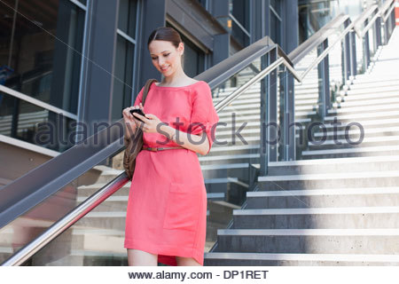 Woman using cell phone on sunny stairs - Stock Photo