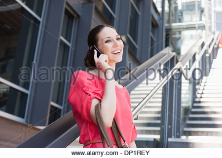 Woman talking on cell phone on sunny stairs - Stock Photo