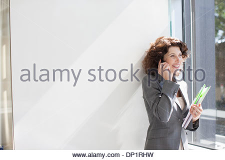Businesswoman talking on cell phone by window - Stock Photo