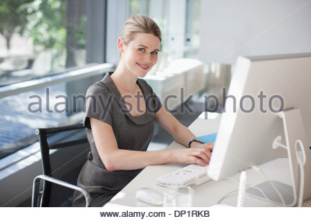 Businesswoman using computer in office - Stock Photo
