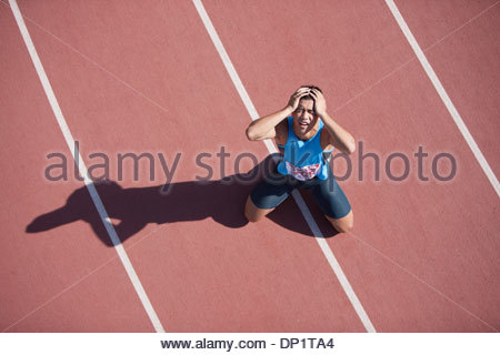 Disappointed runner kneeling on track - Stock Photo