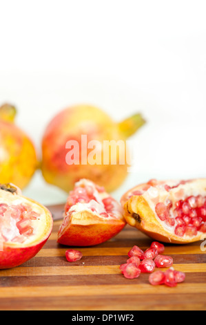 fresh pomegranate fruit on wood over white background - Stock Photo