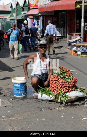 Litchis street seller, Port Louis, Mauritius. - Stock Photo