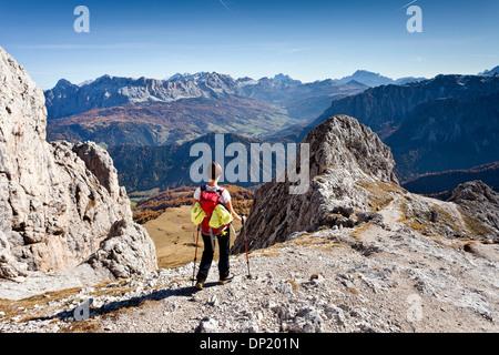 Mountain climber descending from Peitlerkofel Mountain in Puez-Geisler Nature Park, overlooking Val Badia valley, - Stock Photo