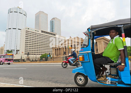 Tuk tuk driver with the building of the Bank of Ceylon at the back, the Old Parliament, right, Colombo, Sri Lanka - Stock Photo