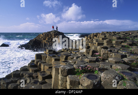People standing on the hexagonal basalt columns of the Giant's Causeway, County Antrim, Northern Ireland. - Stock Photo