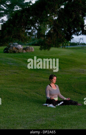 May 24, 2006; Sacramento, CA, USA; Amanda Amburgey of San Jose meditates outdoors as the sun sets over the Ocean - Stock Photo