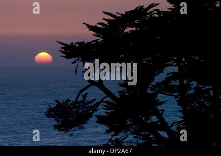 May 24, 2006; Sacramento, CA, USA; The sun sets over the ocean and the cypress trees at Esalen Institute in Big - Stock Photo