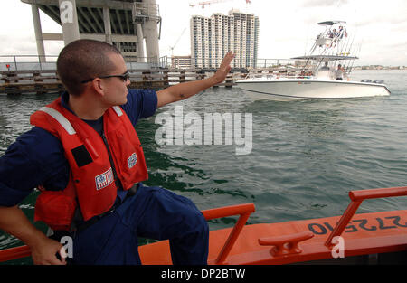 May 26, 2006; Riviera Beach, FL, USA; Cost Guard BM3 Chris Stover, 23, of Palm Beach Gardens waves to a passing - Stock Photo