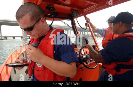 May 26, 2006; Riviera Beach, FL, USA; Coast Guard BM3 Chris Stover, 23, of Palm Beach Gardens radio's in information - Stock Photo