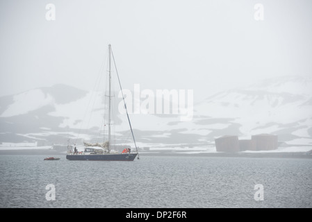 ANTARCTICA - A yacht, the Elincia, comes in to anchor near the shore of Whalers Bay on Deception Island with snow - Stock Photo