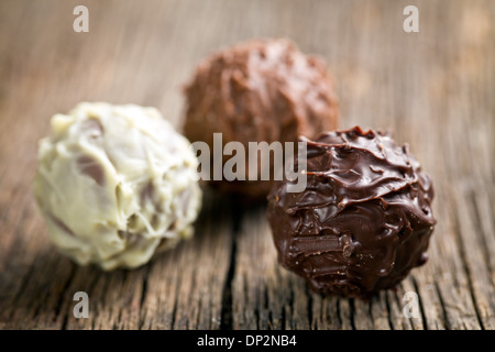 various chocolate balls on wooden background - Stock Photo