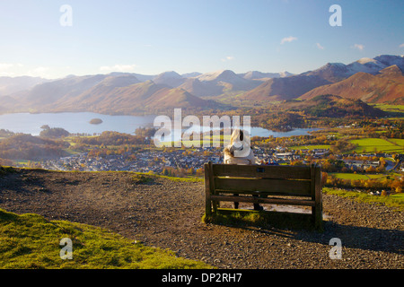 Female walkers sitting on a bench looking at the view above Derwent Water in the Lake District National Park, UK - Stock Photo