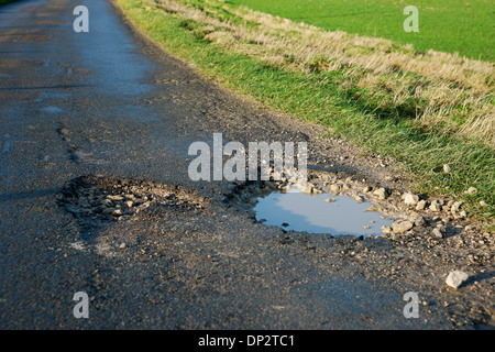 Pothole in the road filled wth water England UK United Kingdom GB Great Britain - Stock Photo