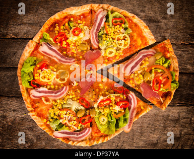 Whole gourment pizza on the wooden table, from above  - Stock Photo
