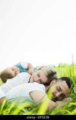 Family Sleeping in Grass, Mannheim, Baden-Wurttemberg, Germany - Stock Photo