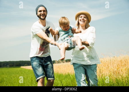 Parents Swinging Baby Daughter by Agricultural Field, Mannheim, Baden-Wurttemberg, Germany - Stock Photo