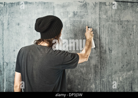 Graffiti artist in black clothes spraying the wall/ - Stock Photo