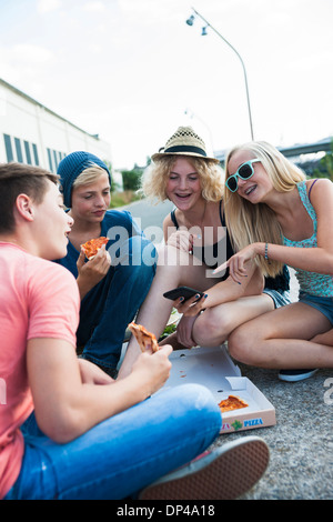 Group of Teenagers sitting on ground outdoors, eating pizza and hanging out, Germany - Stock Photo