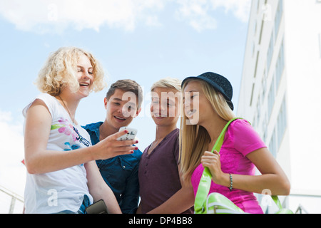 Group of teenagers standing outdoors looking at cell phone and talking, Germany - Stock Photo