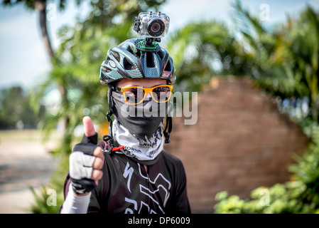 Cycling competitor wearing a GoPro Hero 3 helmet mounted digital video camera to record his event. Thailand S. E. - Stock Photo