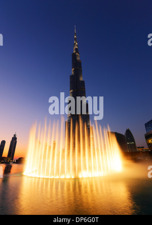 Dubai, Burj Khalifa and illuminated fountain. - Stock Photo