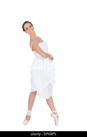 Smiling young ballet dancer standing on her tiptoes - Stock Photo
