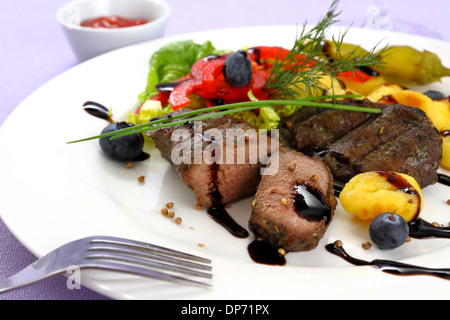 Lamb steak with potato, vegetable and balsamic sauce, close up - Stock Photo