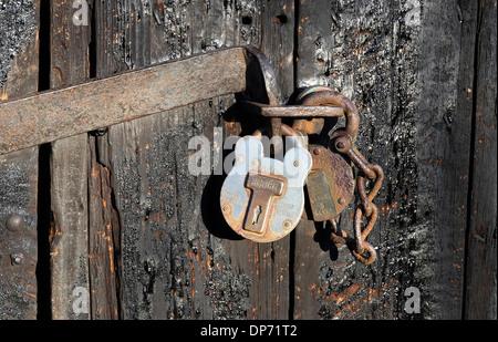 two padlocks on old garage door, norfolk, england - Stock Photo