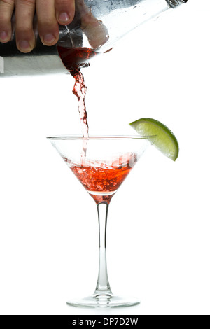 male hands pouring a vodka cocktail in to a chilled martini glass with a llime garnish - Stock Photo