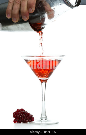 action shot of a bar tender pouring a pomegranate martini isolated on a white background - Stock Photo