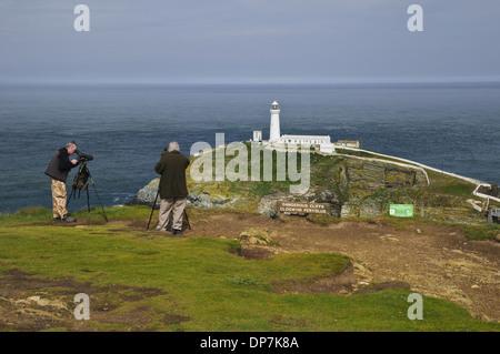 Birdwatchers using spotting scopes to view nesting seabirds on cliffs beside 'Dangerous Cliffs Clogwyni Peryglus' - Stock Photo