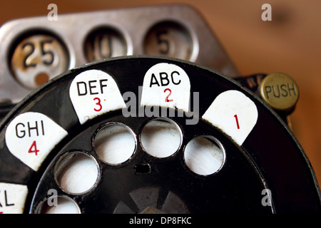 Close up image of an antique rotary pay phone isolated on a white background. - Stock Photo