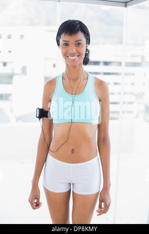Attractive sportswoman listening to music - Stock Photo